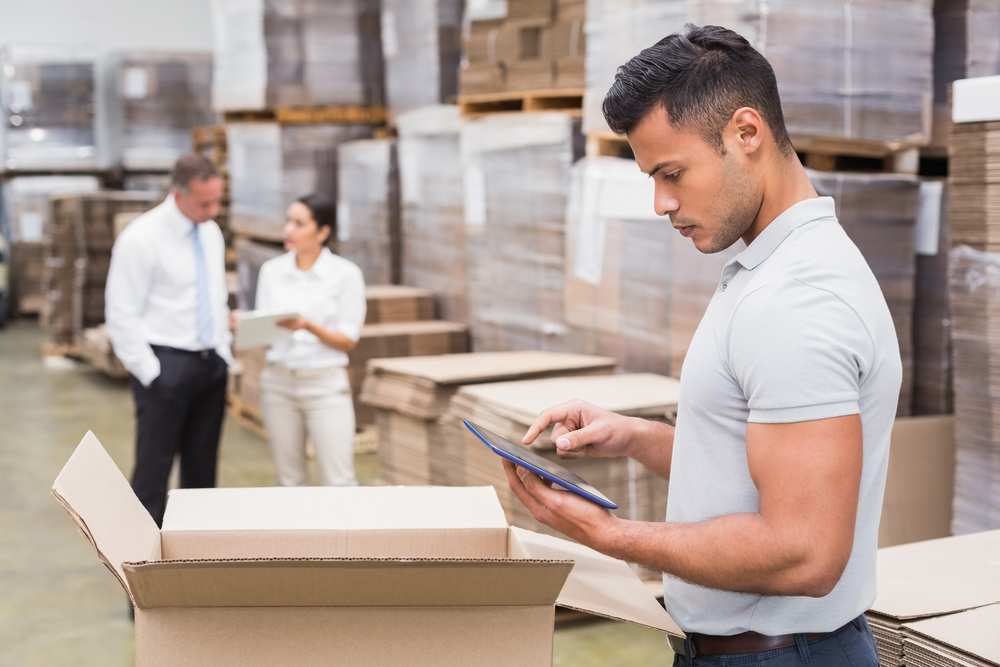 Portrait of male manager using digital tablet in warehouse